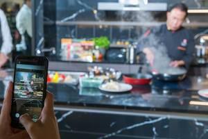 Food photography: Smartphone-Bild des chinesischen Kochs Martin Yan während einer Live-Kochshow