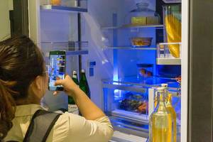 Food Photography: Woman takes a picture of the filled fridge interior