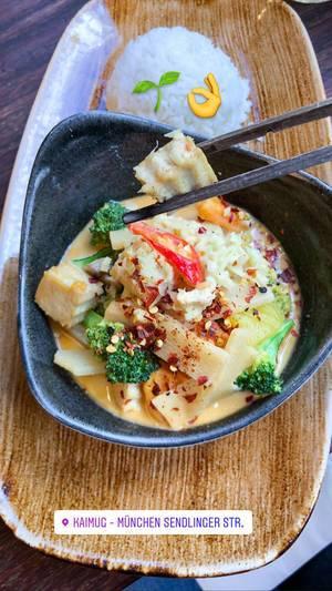 Foodblogger postet ein Instagrambild von veganem Mittagessen im asiatischen Restaurant: Thai-Curry mit weißem Reis
