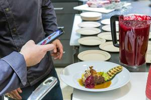 Foodstagram: Man takes picture of a colorful meal, prepared by a WMF chef at IFA-exhibition in Berlin, Germany