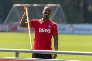 Football player Kingsley Ehizibue enjoys minutes after the training and smiles on the pitch at Geißbockheim, Cologne