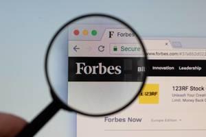 Forbes-Logo am PC-Monitor, durch eine Lupe fotografiert