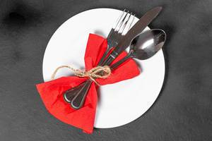 Fork, knife and spoon with red napkin and white plate on black background. Top view (Flip 2019)