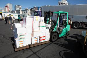 Fork lifter transports fresh food in white isolating boxes in Tokyo, Japan