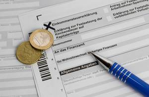 Formular Einkommensteuererklärung mit Kugelschreiber und Euromünzen