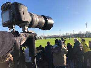 Fotograf mit Canon Kamera und Teleobjektiv am Rande eines Fußballtrainingplatzes