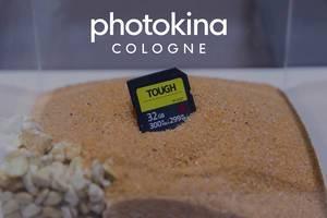 """Fotografiezubehör: Tough 32GB Speicherkarte steckt im Sand, unter dem Bildtitel """"photokina Cologne"""""""