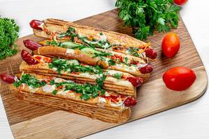 Four hot dogs on the kitchen Board with fresh herbs and tomatoes. Top view (Flip 2019)