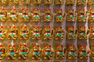 Four rows of Japanese golden beckoning cats as fortune bringers in coa Wok & Bowl restaurant in Cologne