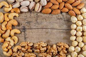 Frame made of different nuts on an old wooden background with free space, top view
