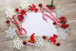 Frame of Christmas decor and white snowflakes on wooden background with free space