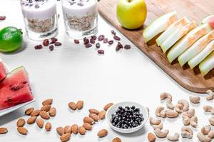 Frame of fruits, oatmeal and nuts for a healthy breakfast on a white wooden background (Flip 2019)