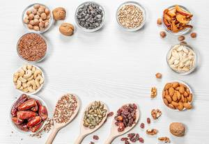 Frame of health food ingredients on white wooden background. Nuts, seeds, dried fruits (Flip 2019)