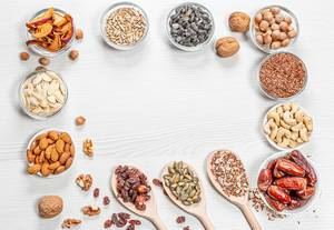 Frame of health food ingredients on white wooden background. Nuts, seeds, dried fruits