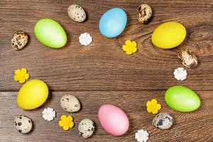 Frame of multicolored Easter eggs on a brown wooden background