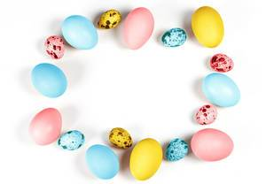 Frame of multicolored quail and chicken eggs on a white background. Free space for Easter greetings (Flip 2020)