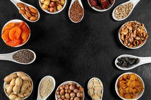 Frame of nuts, dried fruits and seeds on a black background with free space (Flip 2020)