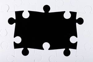 Frame of white puzzles on a black background with free space (Flip 2020)