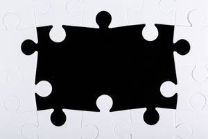 Frame of white puzzles on a black background with free space