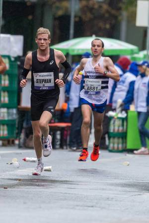 Frankfurter Marathon: Zwei fitte Athleten laufen hintereinander hinter einer Verpflegungsstation