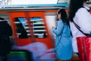 Frau am Bahnhof wartet auf den schnell vorbeifahrenden Zug