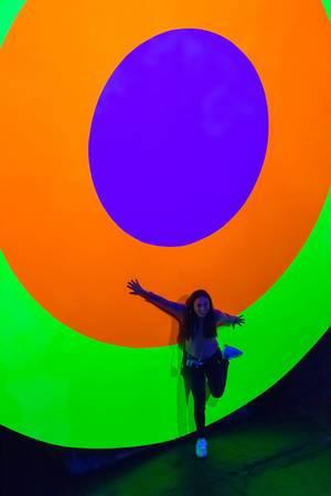 Frau an Zielscheibe mit farbigen, leuchtenden Kreisen an der Photokina in Köln