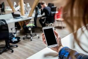 Frau blickt im Büro auf ihr Smartphone