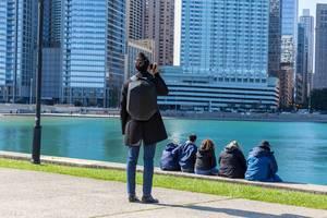 Frau fotografiert die Wolkenkratzer in Downtown Chicago mit ihrem Smartphone, während andere Menschen am Wasser sitzen
