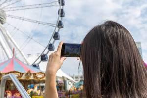"""Frau fotografiert mit ihrem Smartphone das Riesenrad an der Seebrücke """"Navy Pier"""" am Michigansee"""