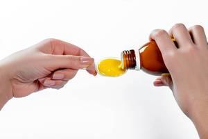Frau gießt flüssige Medikamente wie Hustensaft auf Löffel vor weißem Hintergrund
