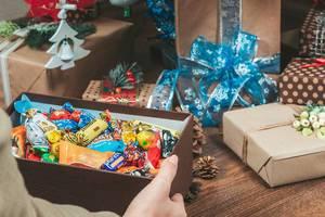 Frau hält einen geöffneten Karton gefüllt mit Süßigkeiten