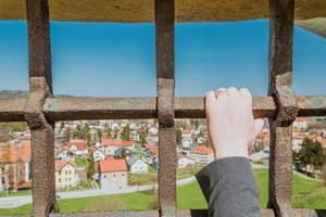Frau hält Fenstergitter in der Hand