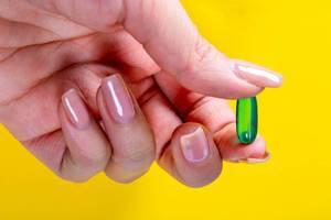 Frau hält grüne Kapsel mit Schmerzmitteln zwischen Fingern vor gelbem Hintergrund