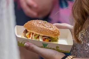 Frau hält Hamburger auf einem kompostbaren Papierteller in ihrem Hand auf dem Tomorrowland Festival