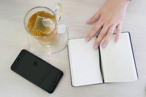 Frau hält ihre Hand auf einem Notizheft mit Smartphne und einer Tasse Teeo