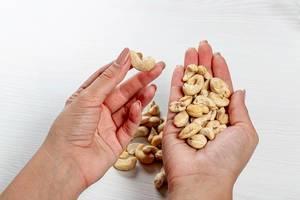 Frau hält rohe Cashewnüsse in den Händen als Symbol der gesunden Ernährung