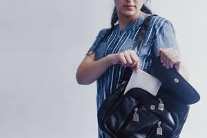 Frau holt aufgrund der Periode eine Monatsbinde aus der schwarzen Handtasche