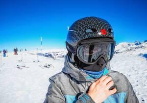 Frau in Skiausrüstung mit Skihelm und Skibrille auf Skipiste in Skigebiet Vars, Frankreich