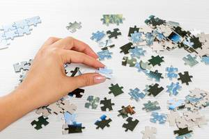 Frau löst ein Puzzle mit vielen Puzzleteilen, auf einem weißen Holztisch