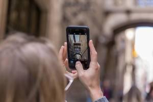 """Frau macht ein Handyfoto der Touristenattraktion und mediterranem Skywalk """"Pont Gòtic"""" in der Carrer del Bisbe in Barcelona, Spanien"""