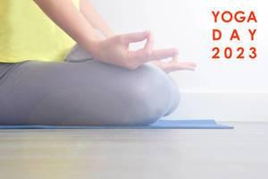 """Frau macht Entspannungsübungen mit Meditation auf einer Yogamatte, neben dem Bildtitel """"Yoga Day 2023"""""""