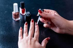 Frau macht Maniküre mit rotem, braunem und schwarzem Nagellack