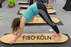 """Frau macht Yoga- und Fitnessübungen auf einem Holzbrett, über dem Bildtitel """"Fibo Köln"""""""