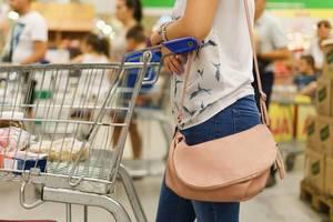 Frau mit Einkaufswage beim Einkaufen im Supermarkt