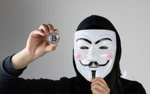 Frau mit Maske hält eine Bitcoin Münze
