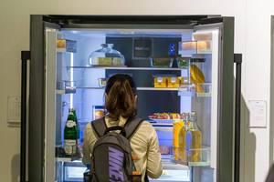 Frau mit Rucksack steht vor einem geöffneten Doppeltür-Kühlschrank und blickt auf gesunde Lebensmittel