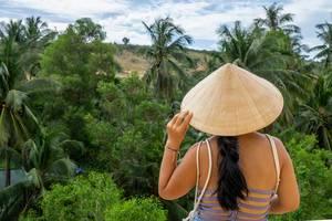 Frau mit typisch vietnamesischem Hut blickt in den Dschungel am Fairy Stream in Mui Ne, Vietnam