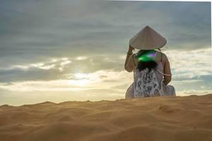 Frau mit typisch vietnamesischem Hut sitzt auf roten Sanddünen in Mui Ne und betrachtet Sonnenuntergang