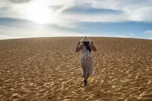 Frau mit vietnamesischem Hut geht über die roten Sanddünen in Mui Ne dem Himmel entgegen