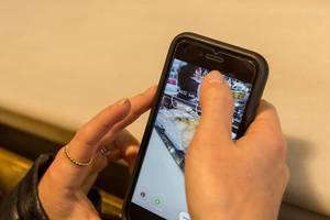 Frau postet auf ihrem Handy ein Foto in ihrer Instagram - Story von der Ladentheke einer Bäckerei in Barcelona (Spanien)